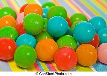 Colorful gum balls on stripe paper.
