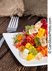 Gummi Bears on a plate as meal with fork (wooden background)