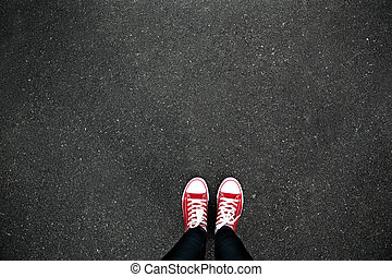 Gumshoes on urban grunge background of asphalt. Conceptual image of legs in boots on city street. Feet shoes walking in outdoor. Youth Selphie Modern hipster