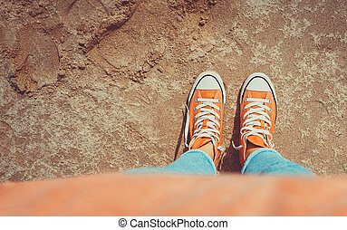 Gumshoes, tennager walking along sand in a sunny day, active lifestyle of a young people, trendy shoes