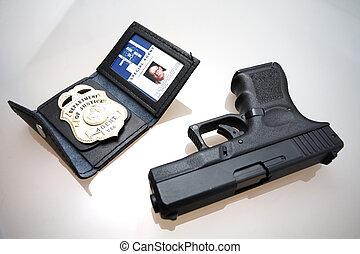 FBI badge and gun.