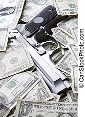 Gun and money - Gun placed on a pile of dollar bills
