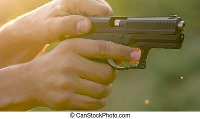 Gun is shot close-up. Man is shooting from a gun