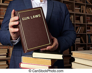 GUN LAWS book in the hands of a jurist. Gun control is one of the most divisive issues in American?politics.
