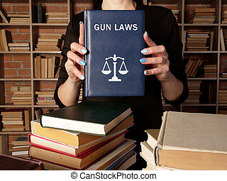 GUN LAWS book in the hands of a lawyer. Gun control is one of the most divisive issues in American?politics.