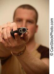 Gun Man - A young man holding a pistol towards the camera.