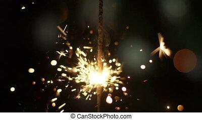 Gun powder sparks shot against dark background. Slow Motion