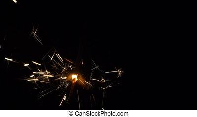 Gun powder sparks shot against deep dark background