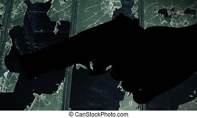 Gun silhouette against broken window crime concept