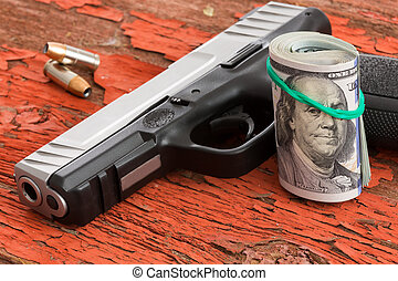 Gun with a roll of 100 dollar banknotes
