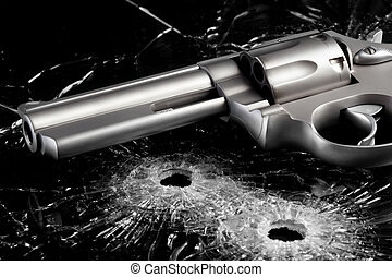 Gun with bullet holes in glass - Gun with two bullet holes...