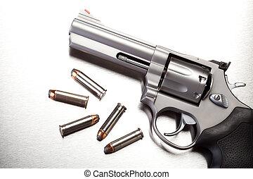 gun with bullets on steel surface - modern revolver handgun