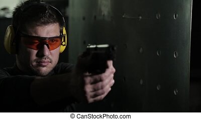 Gunman aiming a pistol in a shooting range - Aiming a pistol...