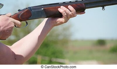 Gunman keeping a shortgun, raising it and shooting on a...