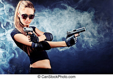 guns - Shot of a sexy military woman posing with guns.