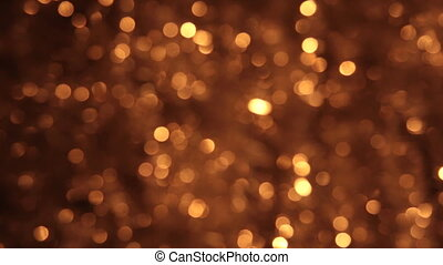 Gusty wind shakes bokeh from gold tinsel. Christmas...