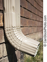 Downspout of a rain gutter showing grass and bricks.