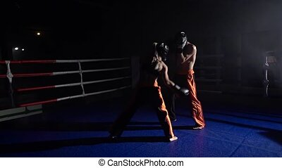Guy and girl in helmets and boxing gloves to fight in the...
