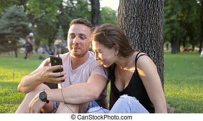 Guy and girl listening to music on the phone in a park under a tree