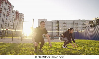 Guy and girl push-ups outdoors. Male and female doing exercises together outdoor. Couple doing sport keeping the body in tension, leaning on the extended arms