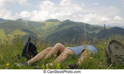 Guy and girl resting in the mountains against the background of clouds