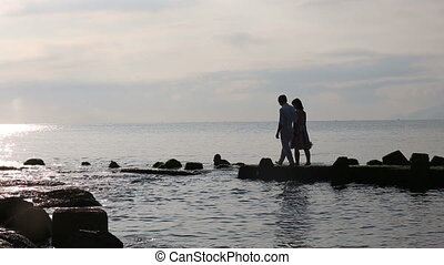 guy and girl walk on rocks in sea and kiss at dawn