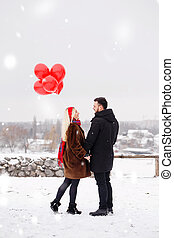 guy and girl with a balloons walking, back view