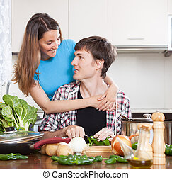 Guy and pretty girl cooking in domestic kitchen