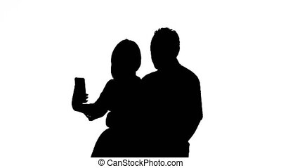 Guy and the girl are making selfies. Silhouette. White...