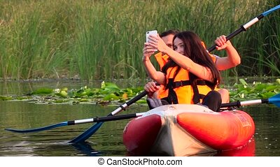 Guy and the girl are sitting in a kayak and make selfie. Slow motion