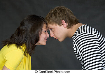Guy and the girl have faced foreheads on a black