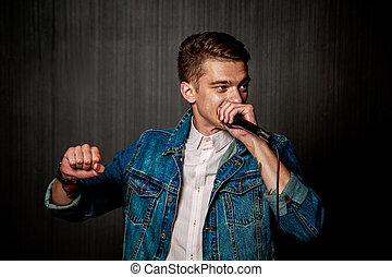 Guy Beat Boxing with Microphone. Dark Background.