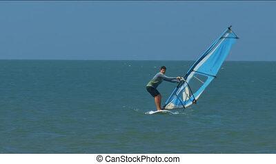 Guy Beginner Tries to Hold Sail Mast against Ocean - guy...