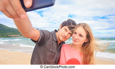 Guy Blond Girl Make Selfie with Red Heart on Beach Wave Surf