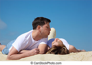 guy blows on lying near to it on sand girl