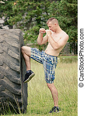 Guy boxing with the tire. Workout
