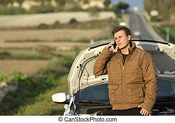 Guy calling roadside assistance for his breakdown car i a country road