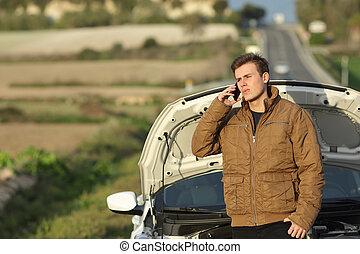 Guy calling roadside assistance for his breakdown car