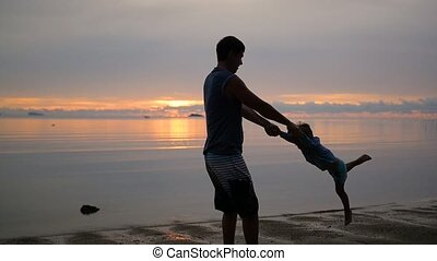 Guy circling baby holding hands on beach at sunset.