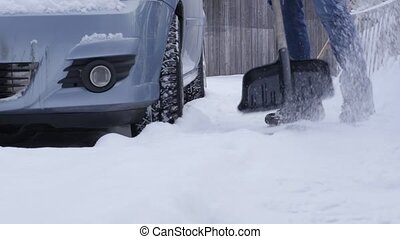 Guy clears snow around car in parking lot in winter after...