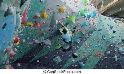 Guy climbing up artificial wall then falling on crash mat in...