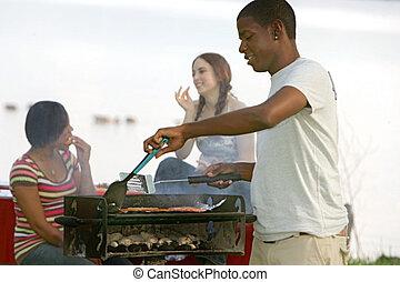 guy cooking bbq - one happy twenties African American male...