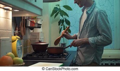 Guy cooking dinner in pot on stove in kitchen. stirs wooden spoon