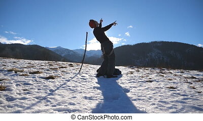 Guy dance against the background of snowy landscape. Male tourist having fun at wintery nature. Young happy man dances funny at the winter mountains. Slow motion Close up.