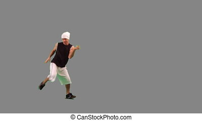 A guy dancing hip-hop against grey background