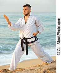 Guy doing karate poses at sunset sea shore