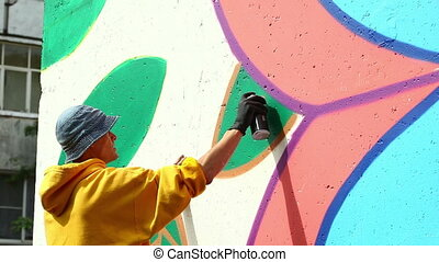 Guy drawing with spray on wall in city park