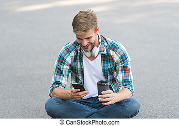 guy drink coffee outdoor. man sit on ground. carefree student in headset use phone. online education. listen music. ebook concept. man checkered shirt. student relax and recharge. coffee to go