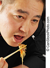 Guy eating glass noodles - Guy wearing black robe eating...