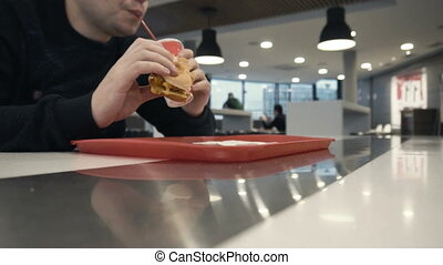 guy eats humburger or chiken burger, drinks sweet carbonated...